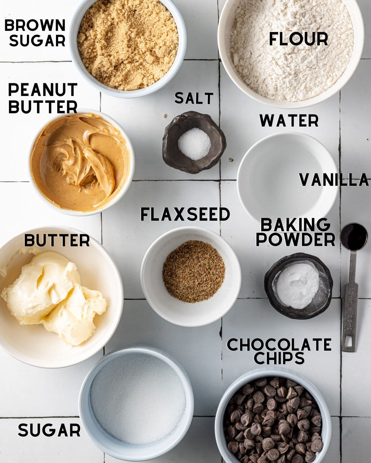 ingredients to make vegan peanut butter cookies in bowls with labels