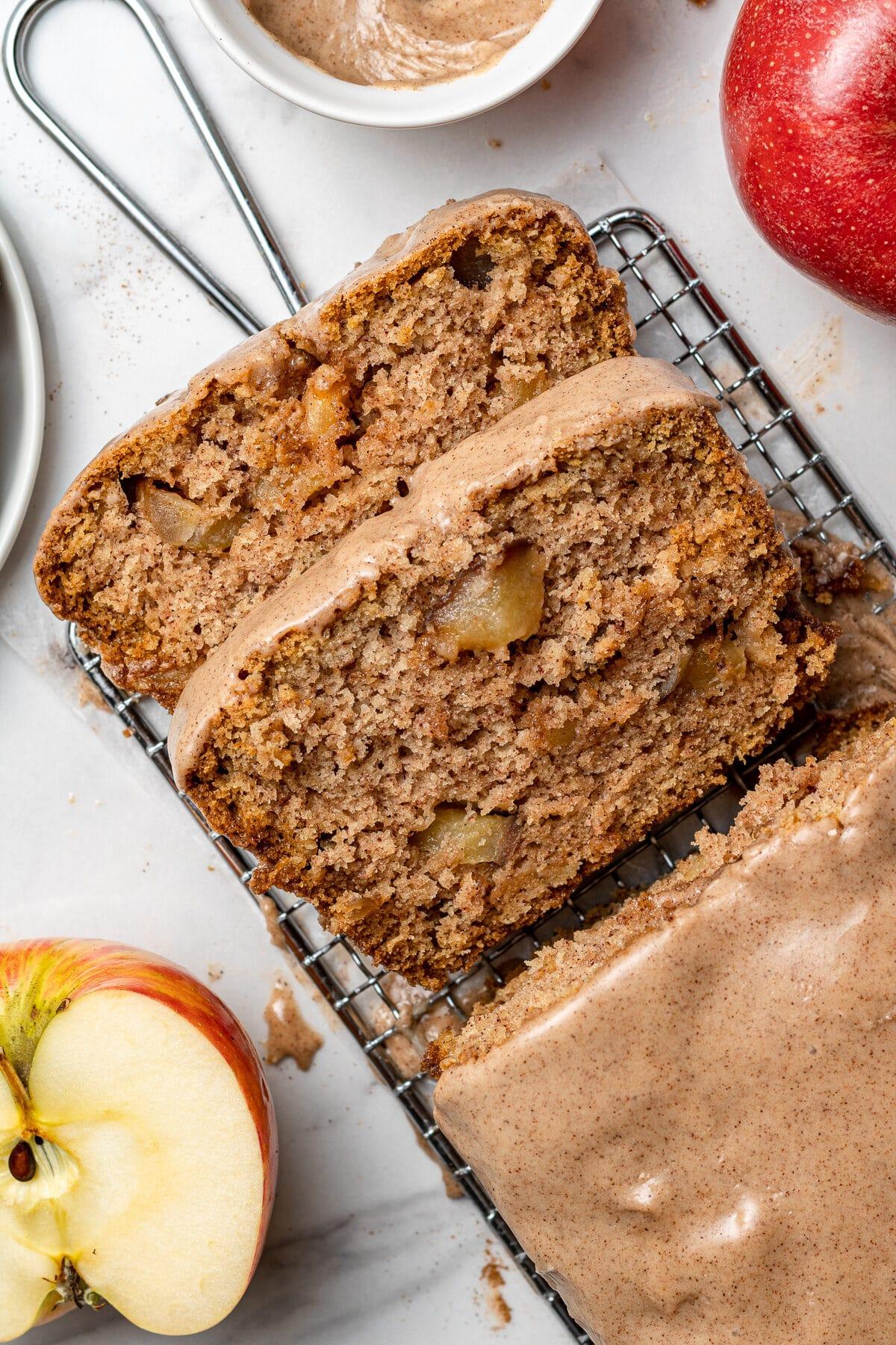 apple cake loaf sliced with half an apple beside it
