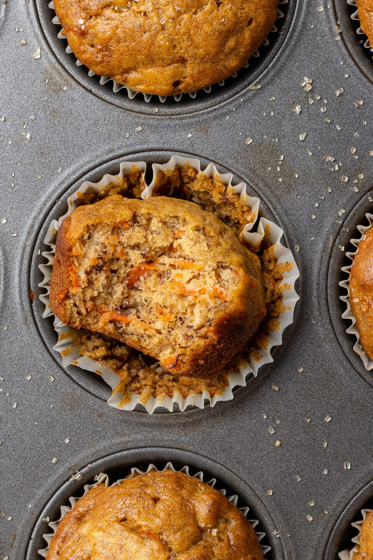 a banana carrot muffin with a bite out of it in a muffin tray
