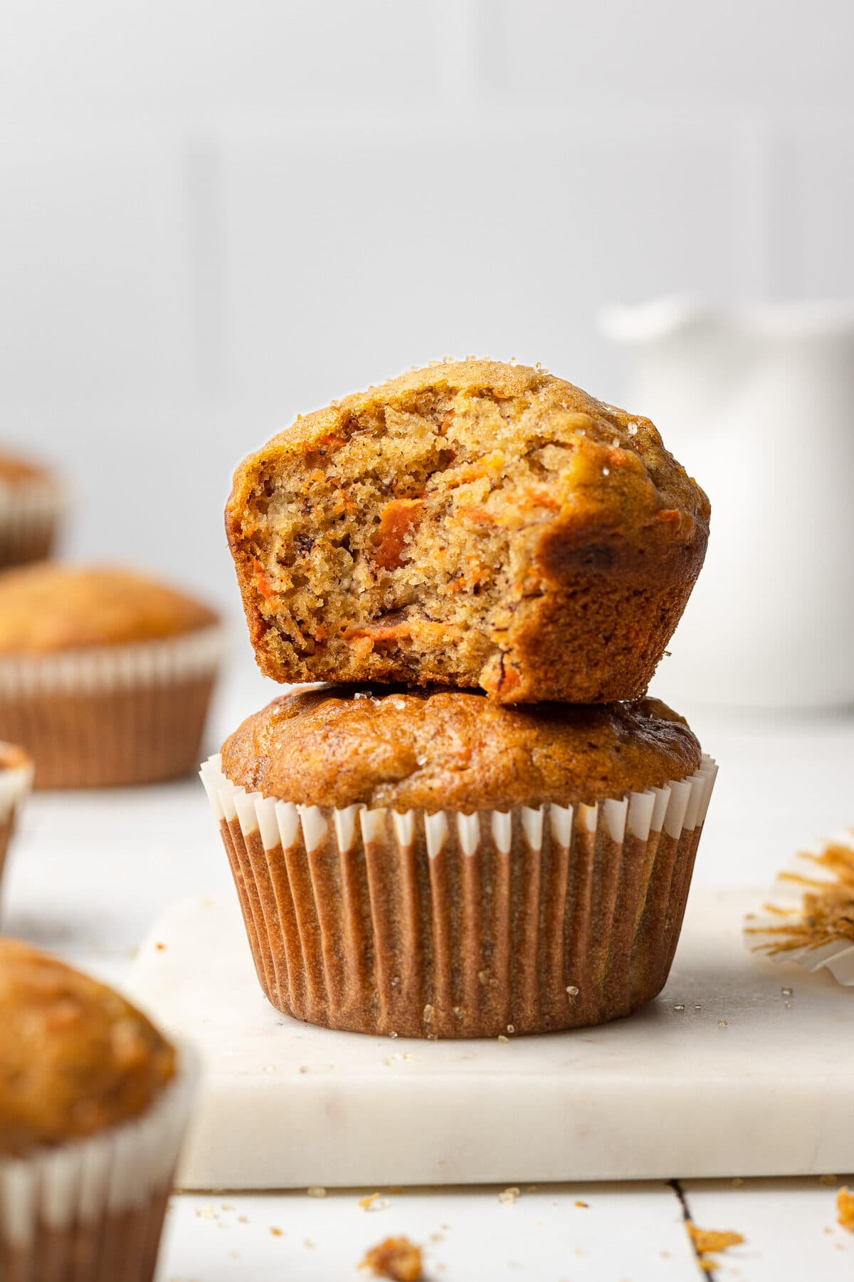 two banana carrot muffins stacked on each other with a bite out of one of them