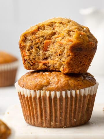 two banana carrot muffins stacked on each other with a bite out of one of the top muffin