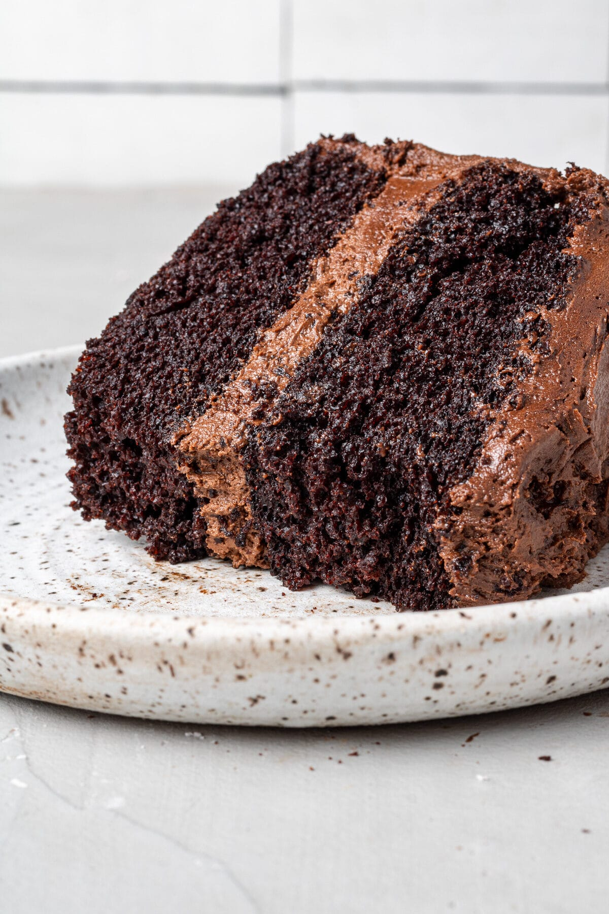 a thick slice of dairy free chocolate cake on a plate