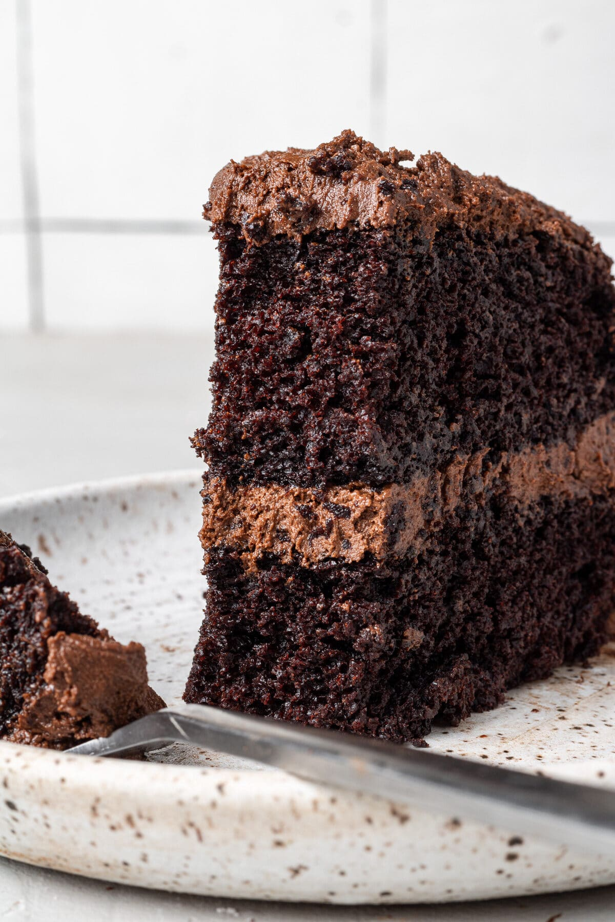 a piece of dairy free chocolate cake on a plate with a bite taken out of it and a fork on the plate