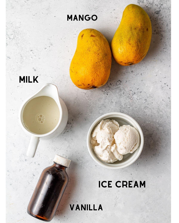 ingredients to make a mango milkshake in bowls labeled