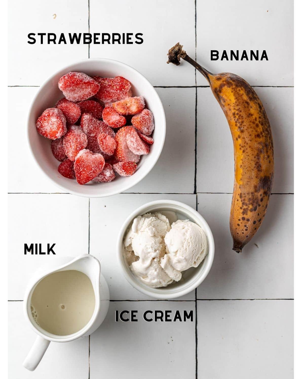 ingredients to make a strawberry banana milkshake in bowls labeled