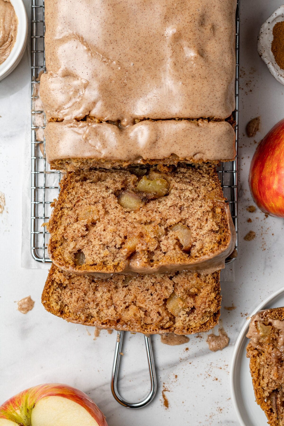 apple cake loaf sliced with half an apple beside it and another slice of apple cake on a plate