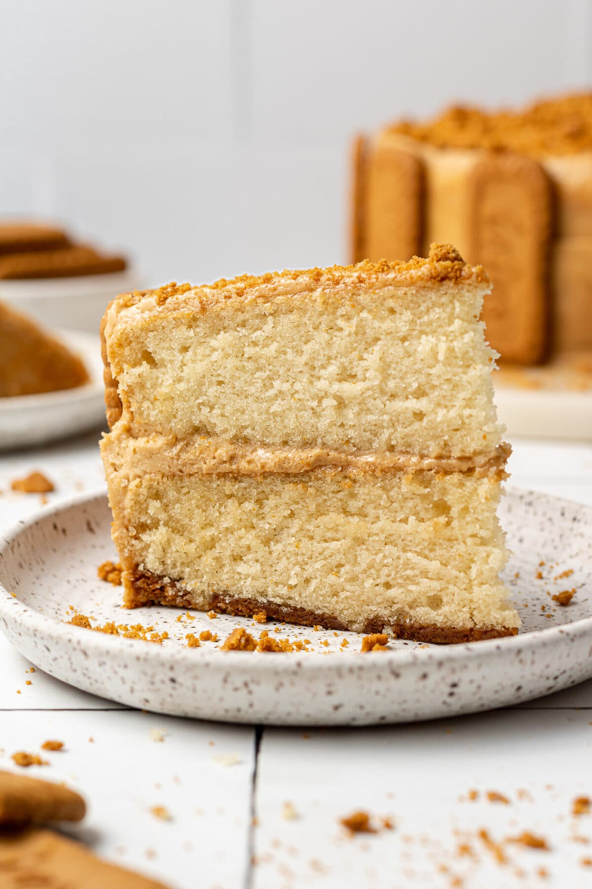 a slice of biscoff cake on a plate with more cake in the background