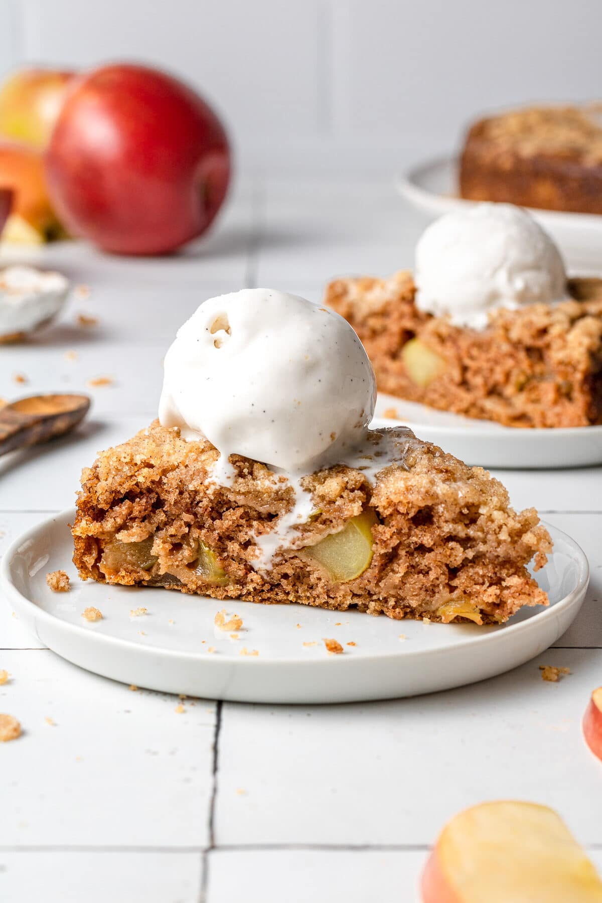a slice of vegan apple cake on a plate with apples in the background an another slice of cake beside it