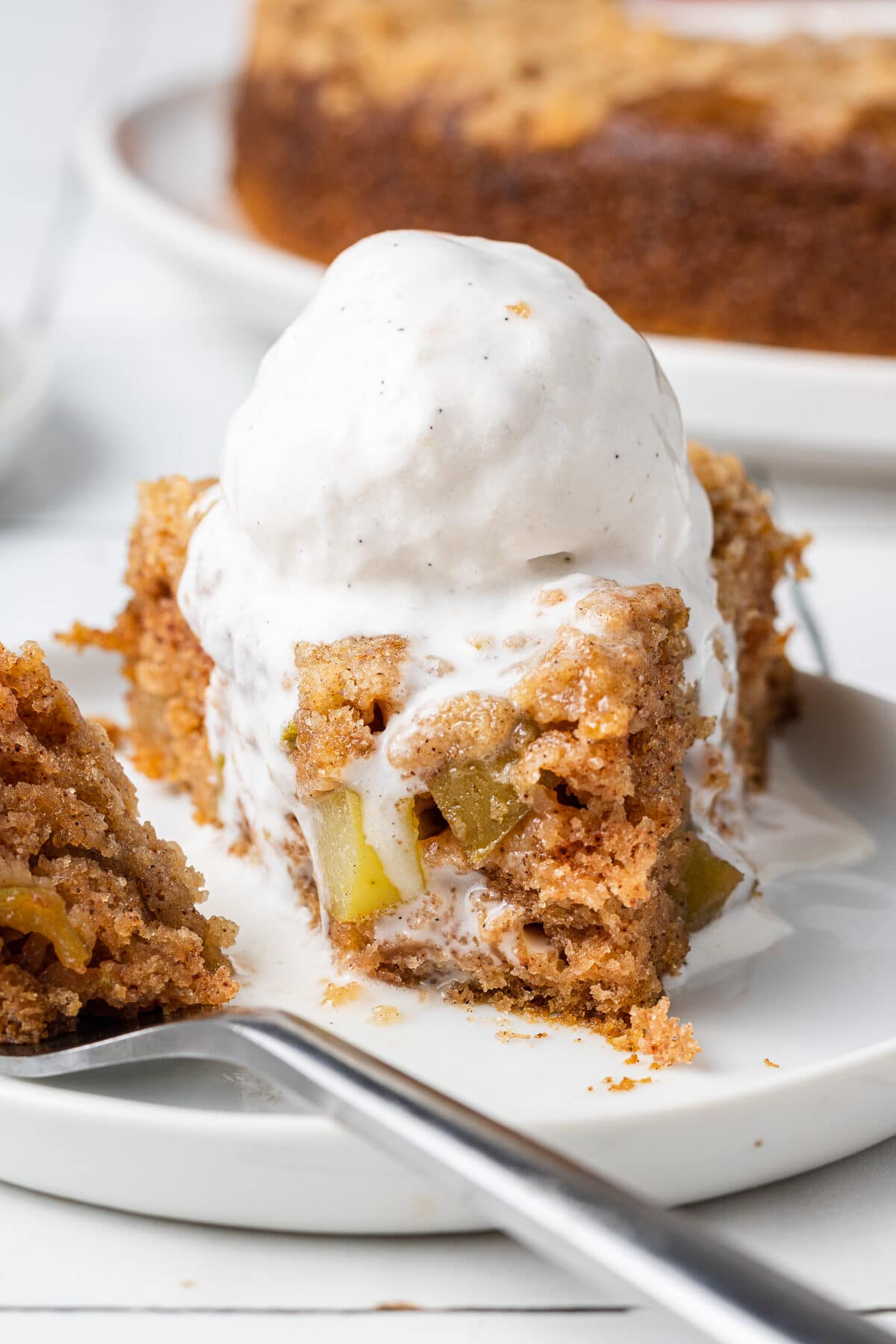 a slice of vgan apple cake on a plate with vegan ice cream melting on top