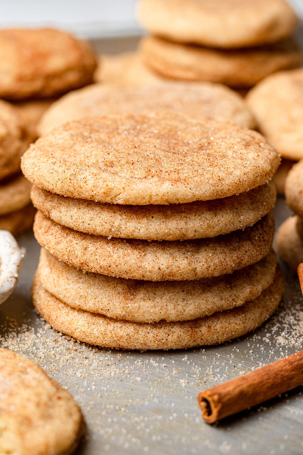 snickerdoodle cookies without cream of tartar stacked on top of each other with a cinnamon stick in the foreground