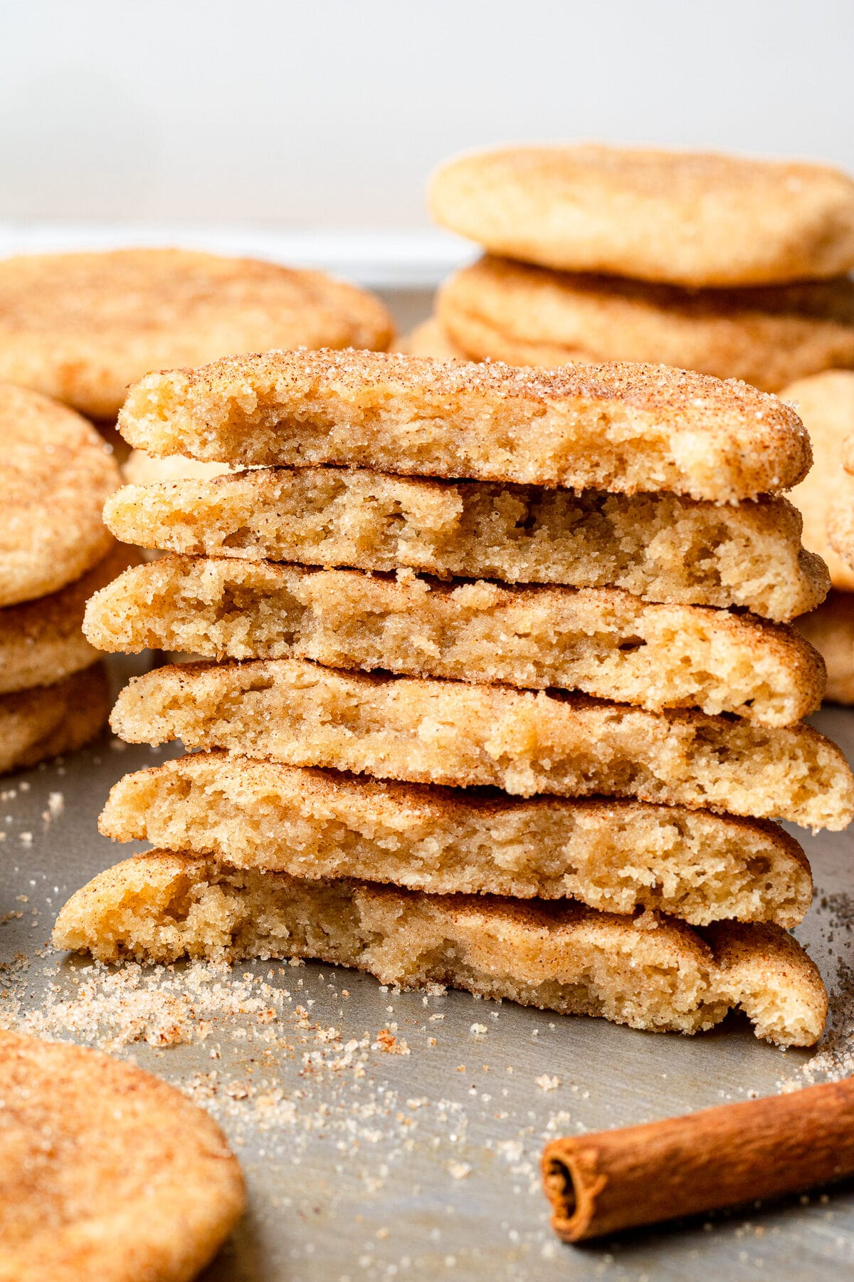 snickerdoodles stacked on top of each other and split in half with more cookies in the background and cinnamon sugar sprinkled around them