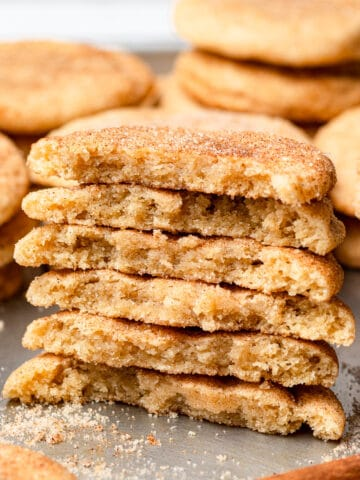 snickerdoodles stacked on top of each other and split in half with more cookies in the background