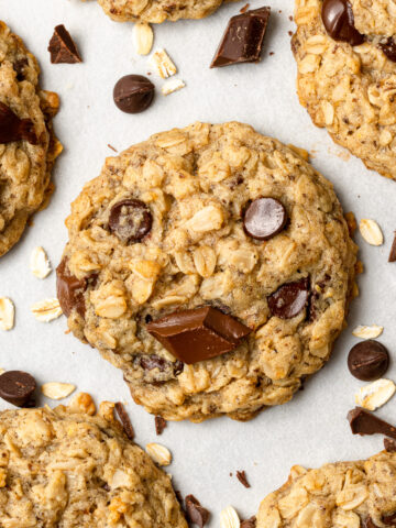 vegan oatmeal cookies on parchment paper with chocolate chips scattered around them